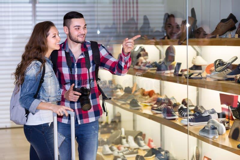 Пары туристов покупая ботинки в моле стоковые фотографии rf