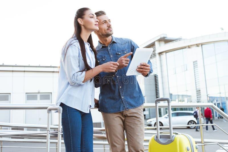 пары туристов с багажом держа цифровой планшет, указывая и стоковое изображение