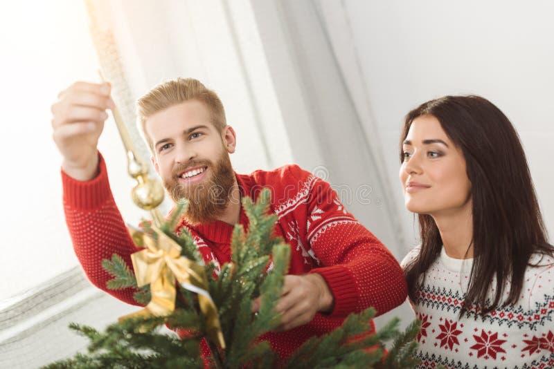 Пары украшая рождественскую елку стоковые фотографии rf