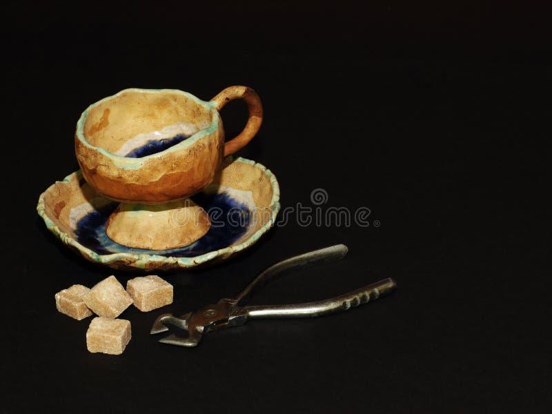 Пары украшенные с поливой, схваты первоначального чая керамические сахара, коричневый кусковатый тростниковый сахар на черной пре стоковое изображение rf
