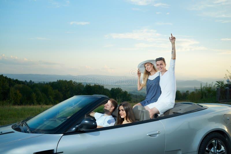 2 пары управляя на роскошном серебряном cabriolet стоковые изображения rf