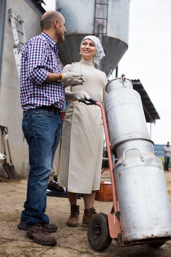 Пары фермеров с чонсервными банками молока стоковое изображение rf