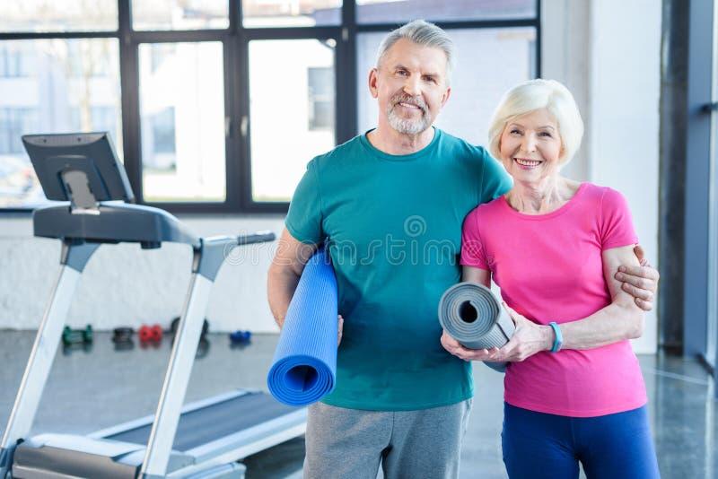 Пары фитнеса держа циновки йоги и усмехаясь на камере в спортзале стоковое фото