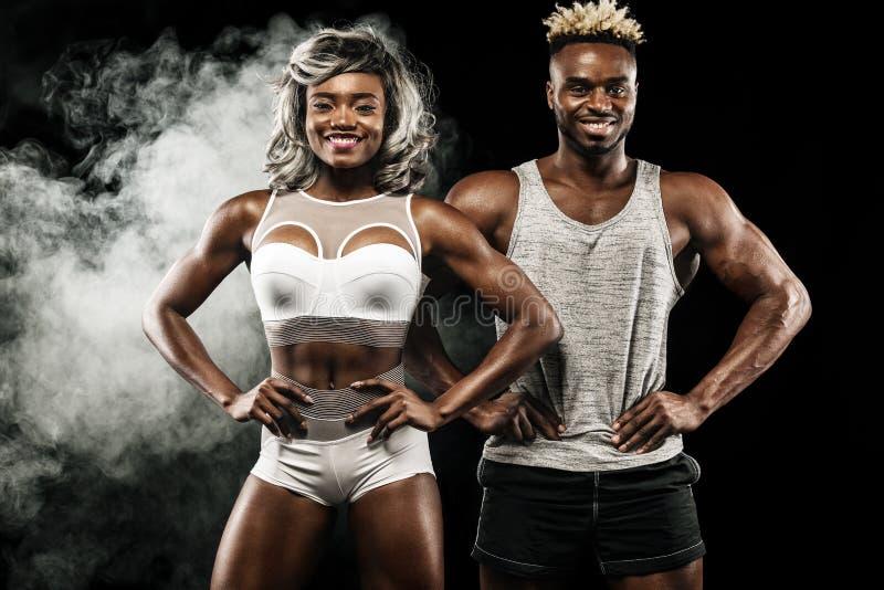 Пары фитнеса спортсменов представляя на черной предпосылке, здоровой заботе тела образа жизни Концепция спорта с космосом экземпл стоковое изображение rf