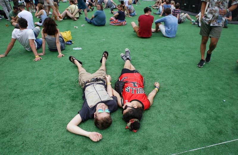 Пары ходоков фестиваля кладя на земной наслаждаясь фестиваль звуколокации стоковая фотография