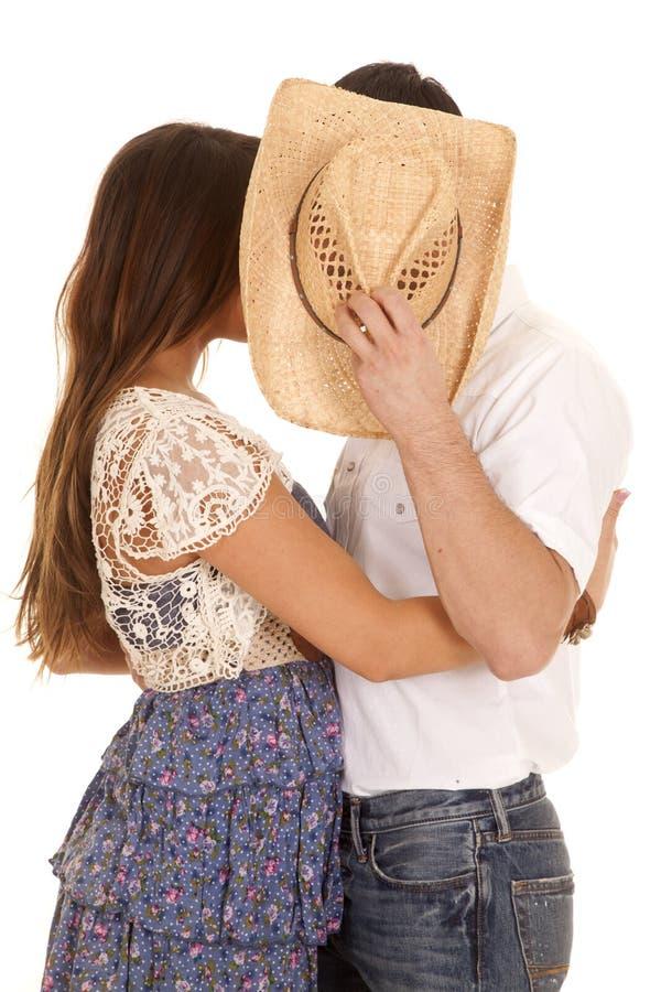 Пары целуют за концом ковбойской шляпы стоковое фото