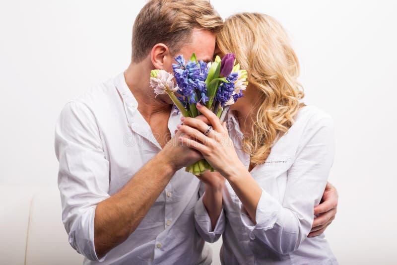 Пары целуя и держа цветки для того чтобы спрятать стоковая фотография
