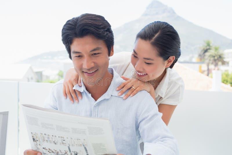 Пары читая газету совместно стоковые изображения