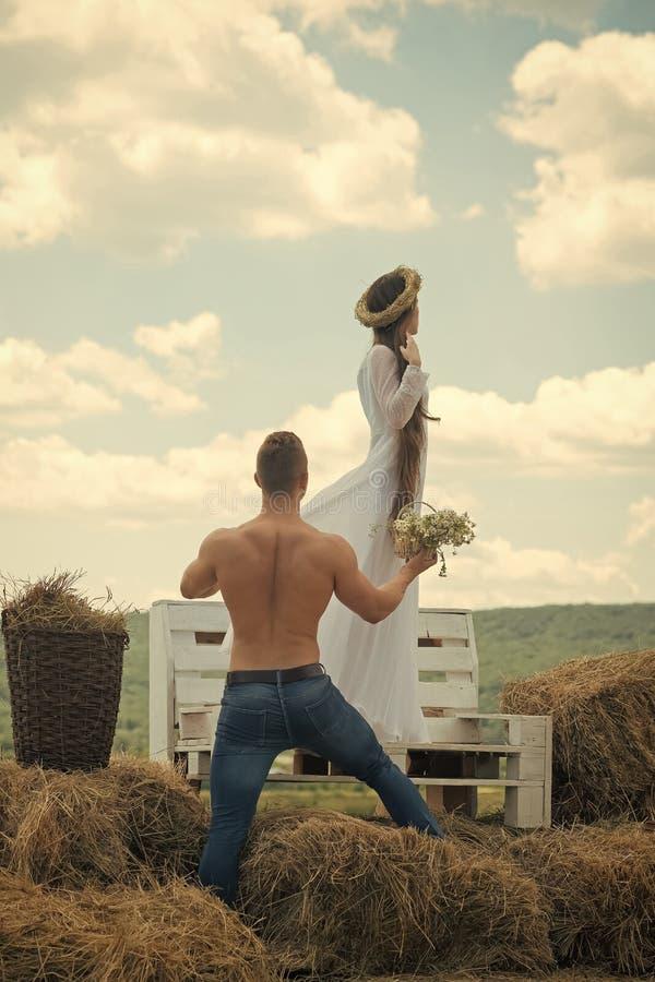 пары чувственные Влюбленность, романс, отношение Человек дает цветки к женщине на стенде Мачо с чуть-чуть торсом и девушкой с стоковые фотографии rf