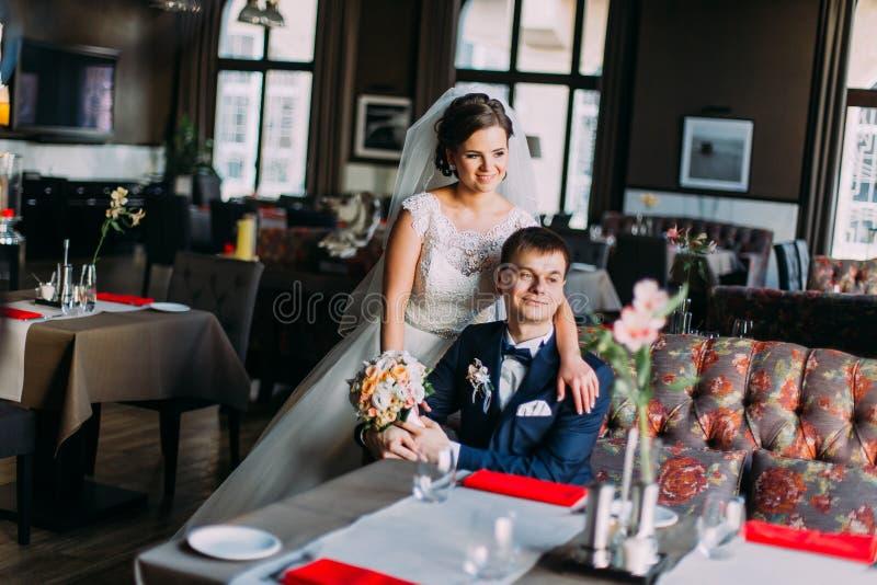 Пары enloved новобрачными Привлекательная молодая невеста в белом платье стоя около сюиты красивого groom голубой представляя вну стоковые фотографии rf