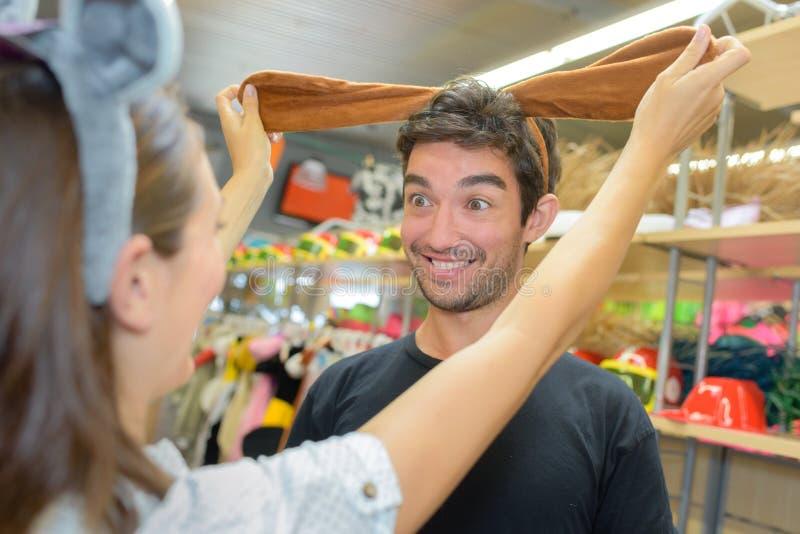 Пары Extatic имея потеху пока ходящ по магазинам в магазине костюма стоковые изображения