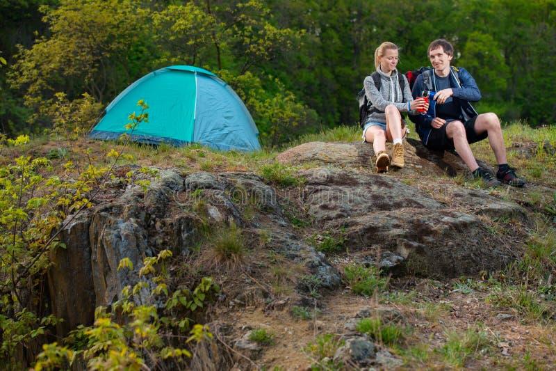 Пары hikers отдыхая с чашкой горячего чая около шатра в th стоковое фото rf
