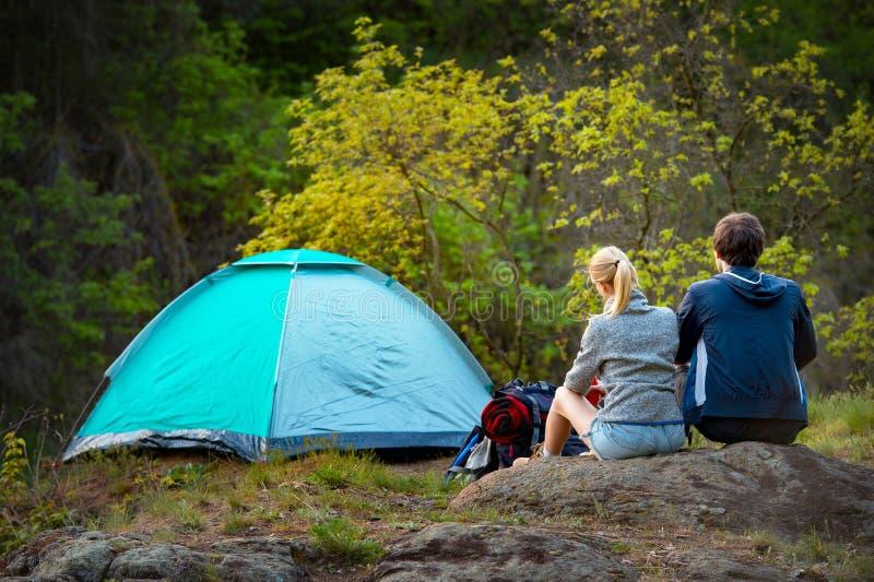 Пары hikers при рюкзаки смотря красивое реку и стоковое фото rf
