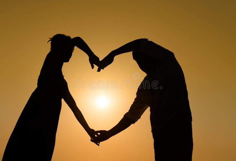 Пары Sillhouette любящие на заходе солнца с сердцем стоковое изображение rf