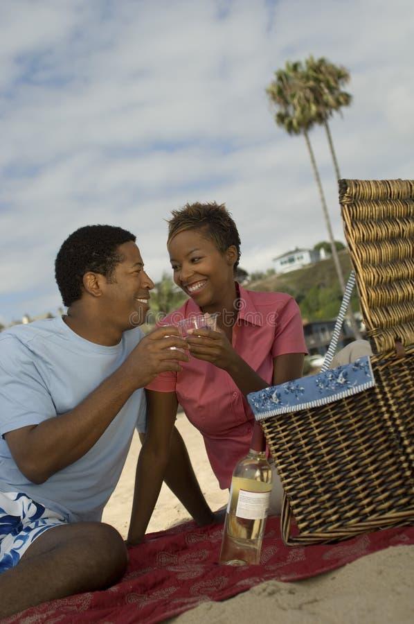 Пары Toasting стекла вина на пляже стоковые фото