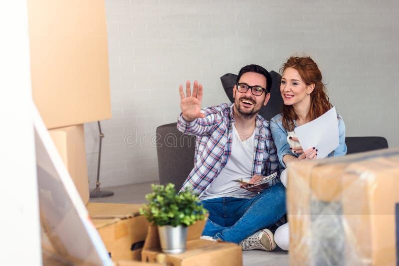 Пары Ung двигая в новый дом Сидеть и ослаблять после распаковывать Смотреть что-то на компьтер-книжке стоковая фотография