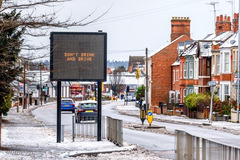 Пасмурный взгляд зимы дня современного знака информации с словами не выпивает и не управляет на типичной английской дороге под сн стоковые изображения rf