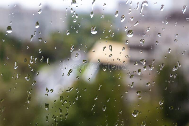 Пасмурный дождливый день летом в городе России Москвы Неожиданное внезапное похолодание, падения на стекле окна и городской пейза стоковое фото rf