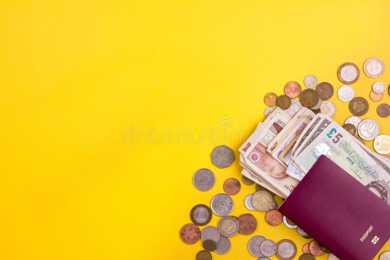 Паспорт с бумажными деньгами и монетками Flatlay каникул на желтой предпосылке стоковая фотография rf