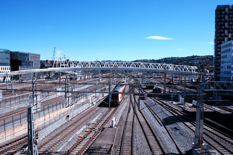 Пассажирский поезд в Норвегии и современном районе города стоковая фотография rf