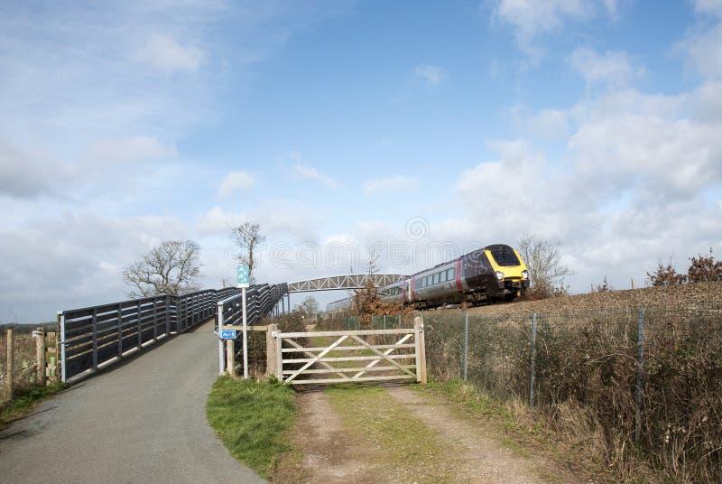 Пассажирский поезд проходя под cycleway и footbridge в Девоне Великобритании стоковая фотография