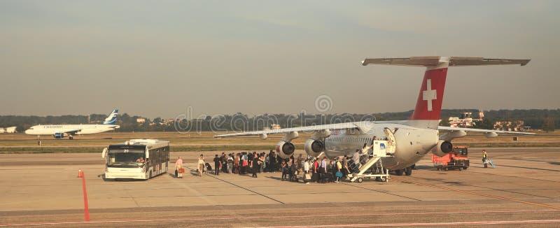 Пассажиры всходя на борт на авиапорте Malpensa. стоковое фото rf