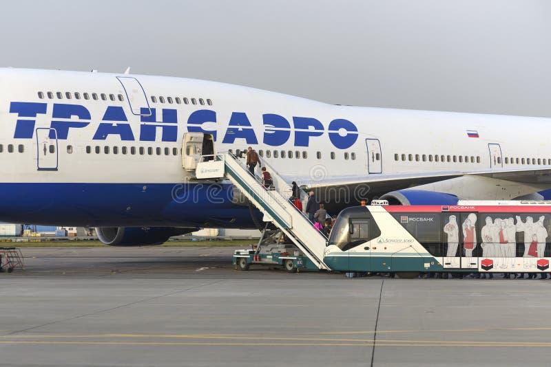 Пассажиры всходят на борт авиакомпаний Боинга 747 Transaero воздушных судн стоковое фото