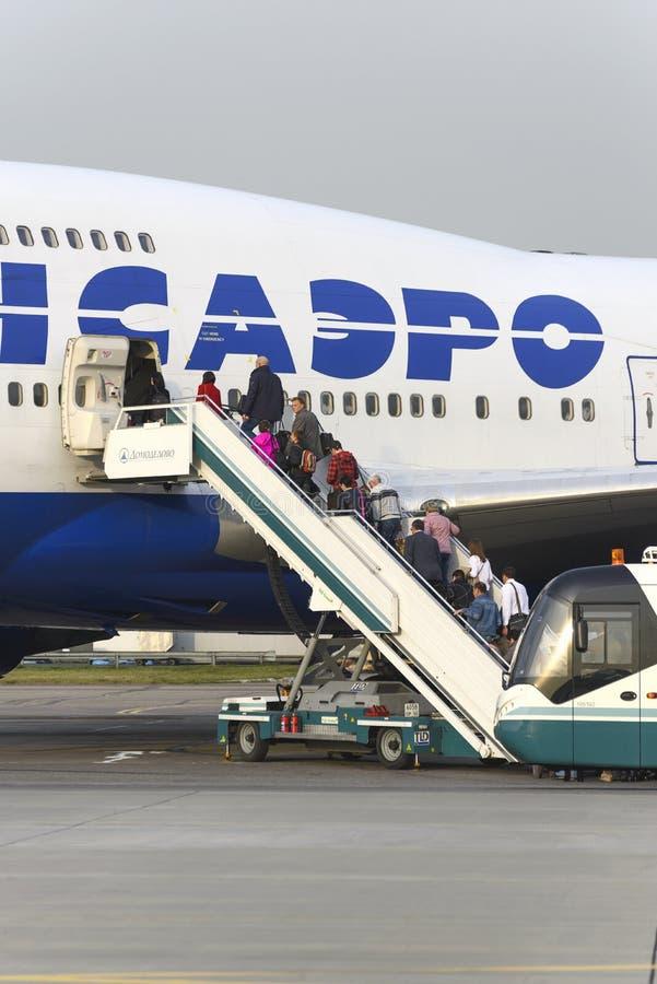 Пассажиры всходят на борт авиакомпаний Боинга 747 Transaero воздушных судн стоковые фото