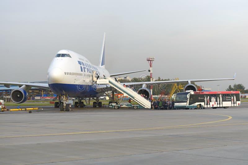 Пассажиры всходят на борт авиакомпаний Боинга 747 Transaero воздушных судн стоковое изображение rf