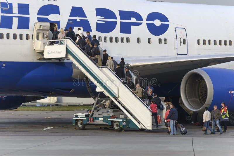 Пассажиры всходят на борт авиакомпаний Боинга 747 Transaero воздушных судн стоковые изображения