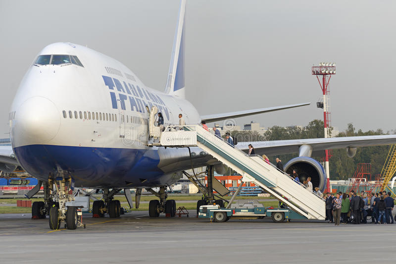 Пассажиры всходят на борт авиакомпаний Боинга 747 Transaero воздушных судн стоковые изображения rf