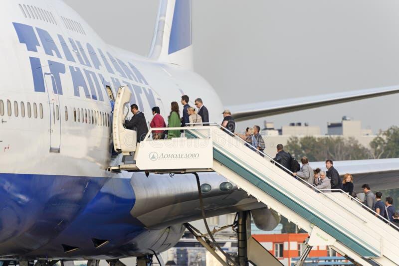 Пассажиры всходят на борт авиакомпаний Боинга 747 Transaero воздушных судн стоковая фотография rf