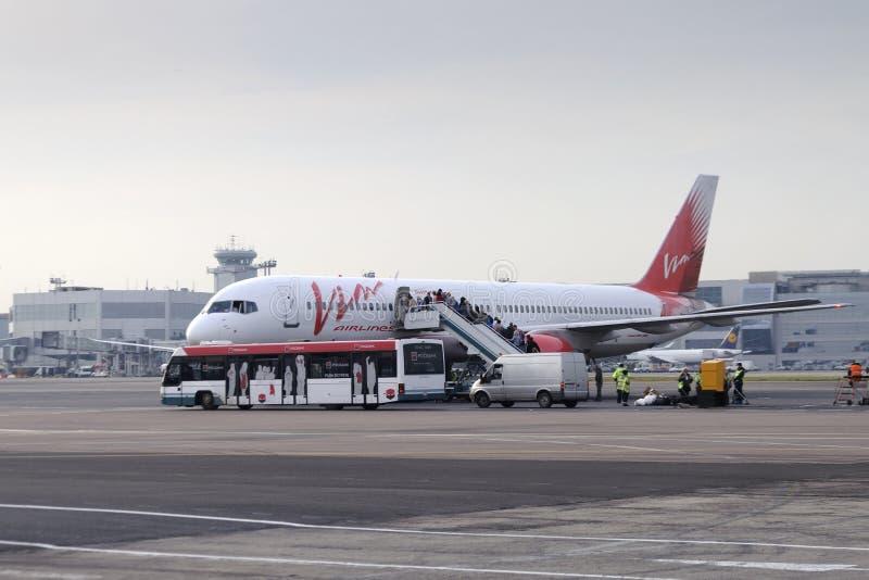 Пассажиры всходят на борт авиакомпаний Vim Боинга 757 воздушных судн стоковые изображения
