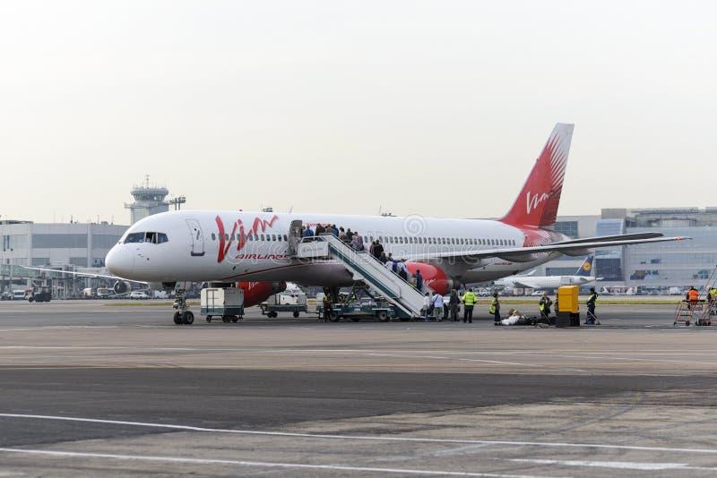 Пассажиры всходят на борт авиакомпаний Vim Боинга 757 воздушных судн стоковое изображение