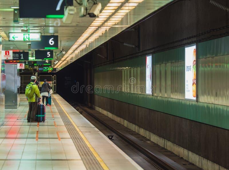 Пассажиры ждать поезд на платформе на станции высокоскоростного рельса THSR Taoyuan Тайваня стоковые фотографии rf