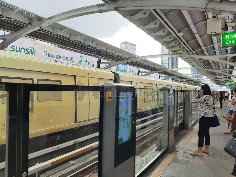 Пассажиры ждут поезд неба или BTS за барьером на станции Chong Nonsi стоковые фото