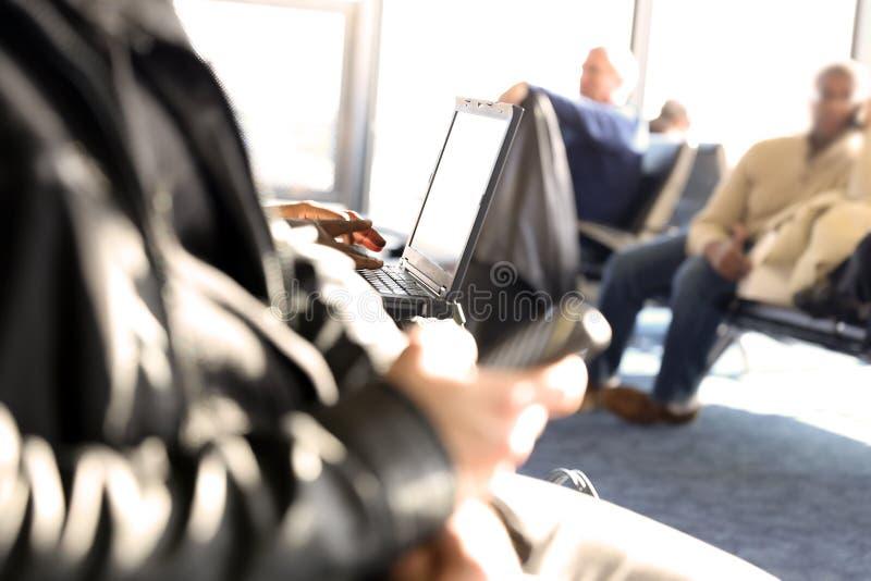 Пассажиры ждать на пассажирах авиапорта используя мобильный телефон стоковая фотография rf