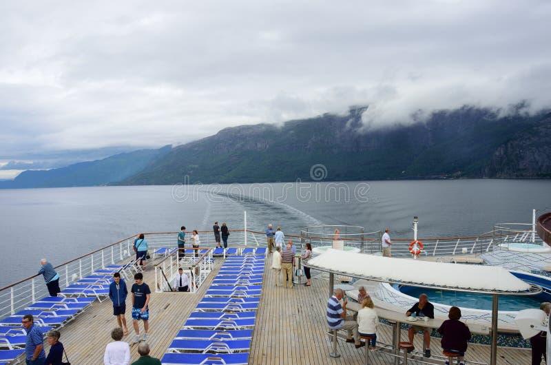 Пассажиры на заде туристического судна наслаждаясь визированием норвежских фьордов стоковое фото rf