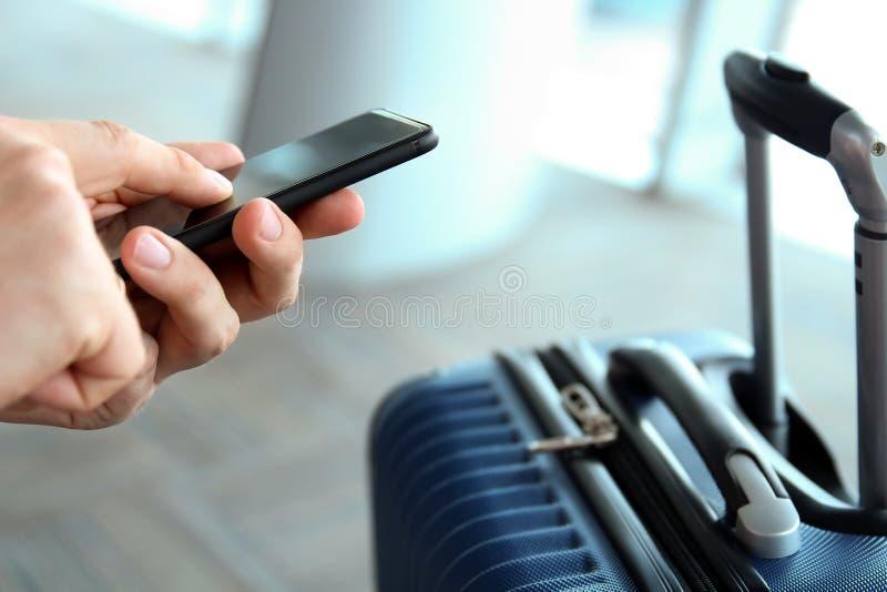 Пассажиры при багаж ждать на пассажире авиапорта используя мобильный телефон стоковые изображения rf