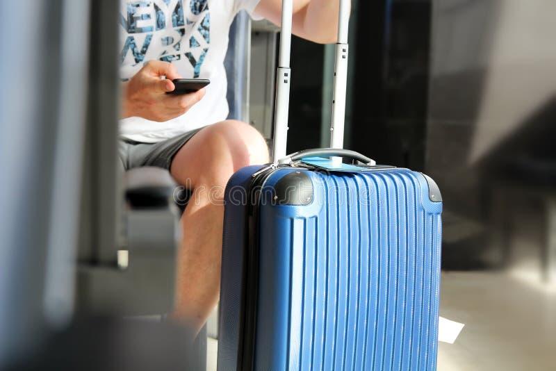 Пассажиры при багаж ждать на пассажире авиапорта используя мобильный телефон стоковые фото