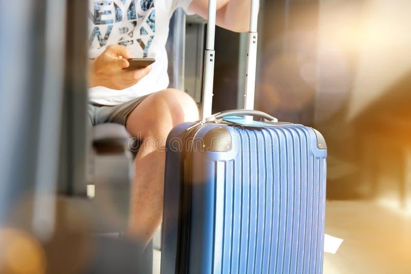 Пассажиры при багаж ждать на пассажире авиапорта используя мобильный телефон стоковая фотография