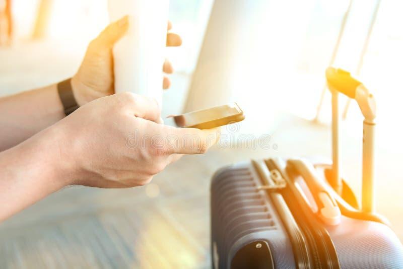 Пассажиры при багаж ждать на пассажире авиапорта используя мобильный телефон и кофе питья стоковая фотография rf