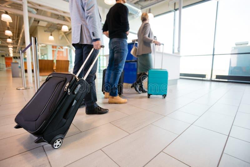 Пассажиры стоя на поле с багажем на приеме a авиапорта стоковые изображения rf