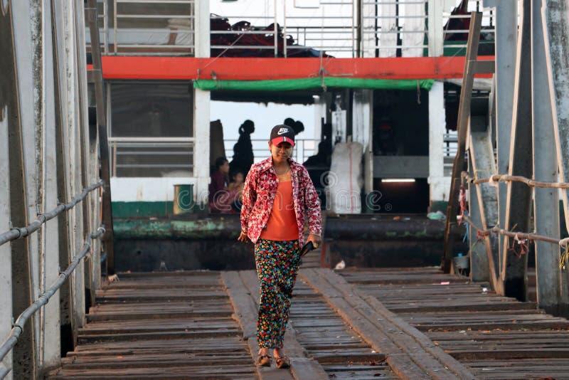 Пассажир женщины Myanmese идя за мостом гавани debark от корабля на реке Янгона стоковая фотография