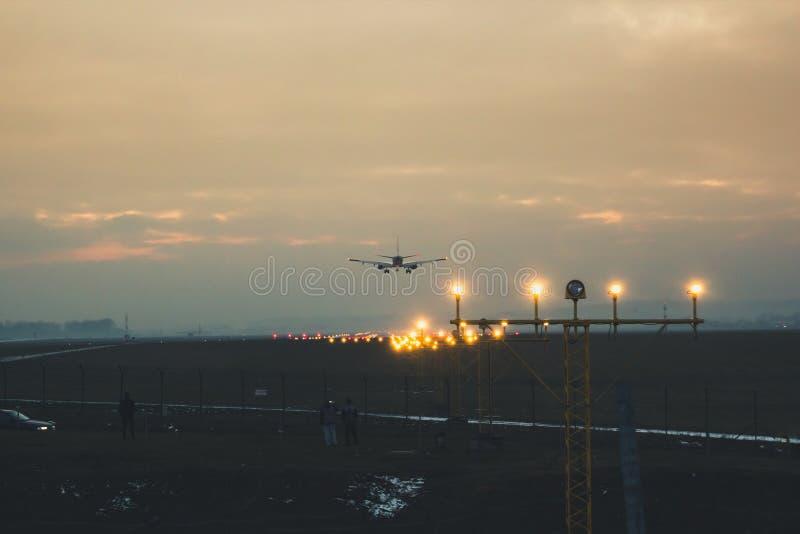 Пассажир или транспортный самолет приземляются на взлётно-посадочная дорожка против backg стоковые изображения