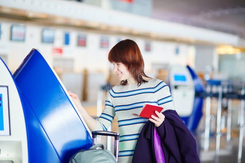 Пассажир на авиапорте, делая само- регистрацию стоковое изображение rf