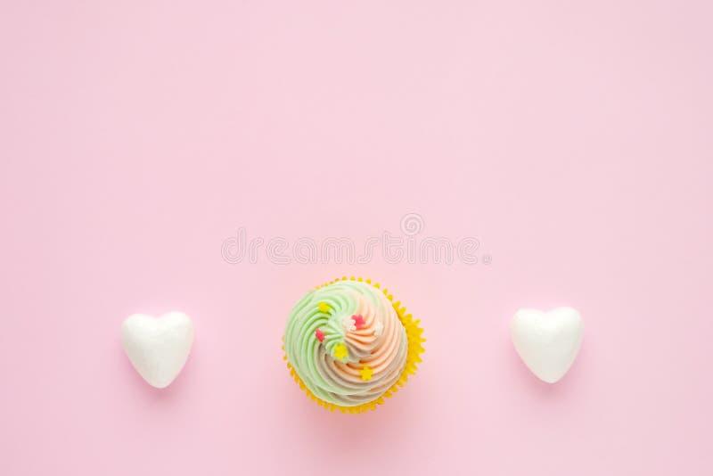 Пастельное пирожное и белые сердца на розовой предпосылке с курортом экземпляра стоковое изображение