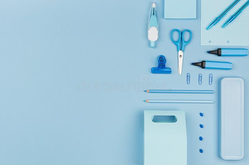Пастельные голубые канцелярские принадлежности офиса цвета установили на голубую предпосылку, искусство концепции для рекламирова стоковая фотография rf