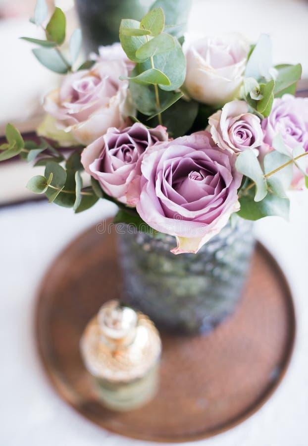 Пастельные розы лета фиолетового, mauve цвета свежие в вазе в cl подноса стоковое фото
