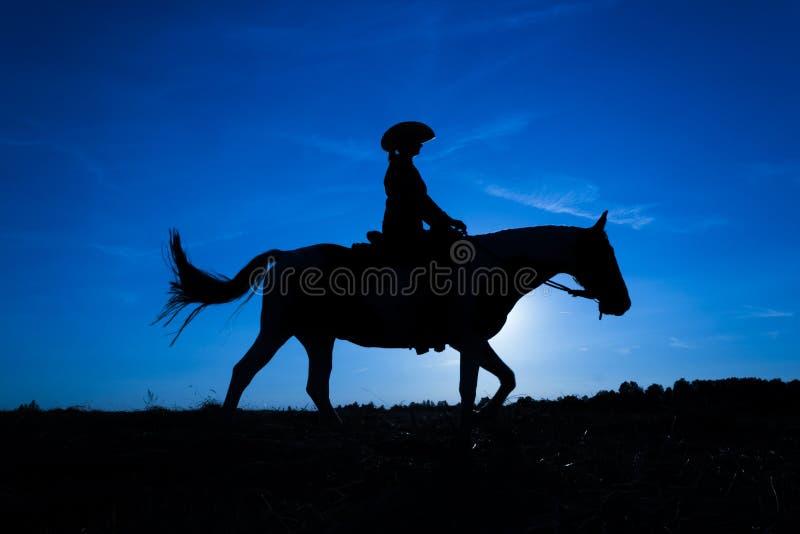 Пастушка силуэта на лошади на заходе солнца в сини 10 стоковое изображение rf